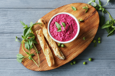 Bowl with delicious creamy beet hummus on wooden board
