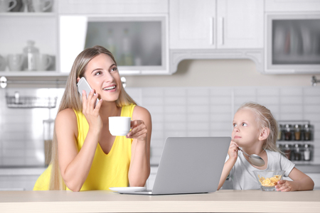 Busy young woman with her daughter at home