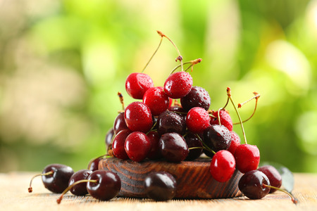 Fresh ripe cherry on wooden table outdoors