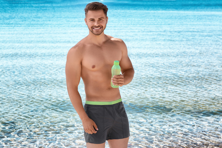 Young handsome man with bottle of water on beach 免版税图像