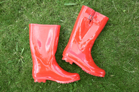 Red rubber boots on green grass Stock Photo
