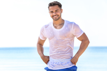 Handsome young man in wet t-shirt on sea beach