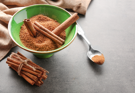 Green bowl with cinnamon sugar and sticks on grey background
