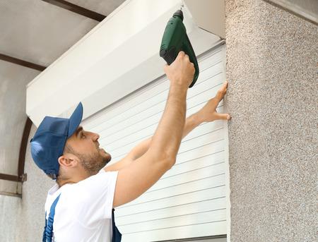 Mężczyzna instalujący roletę na oknie