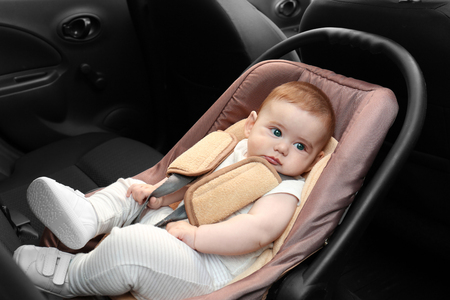 Adorable baby resting in child safety seat inside of car 免版税图像