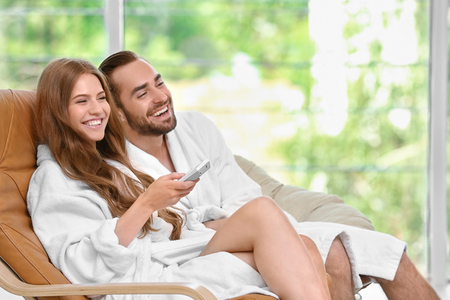 Young loving couple in bathrobes watching television in spa salon