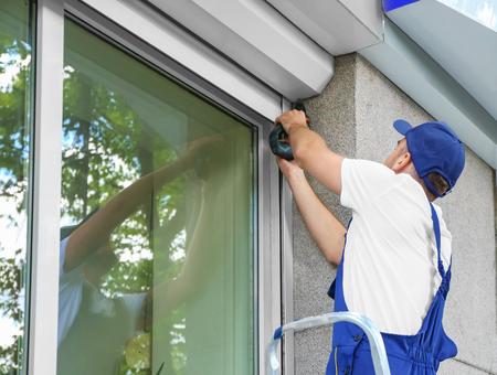 Homme installant le volet roulant sur la fenêtre Banque d'images