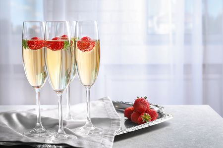 Glasses of delicious wine with strawberry on table