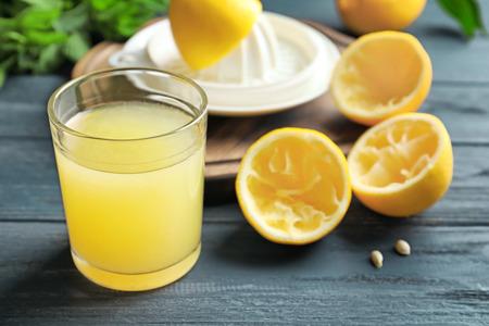 Glass of fresh lemon juice on wooden table Stock Photo