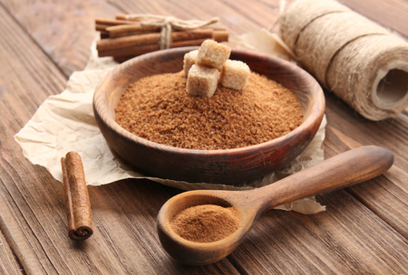 Composition with cinnamon sugar and powder on wooden background