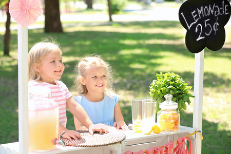 Two cute girls selling lemonade at stand in park