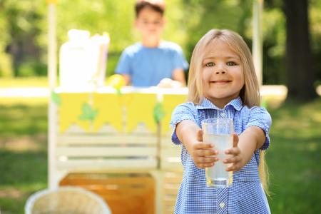 Adorable girl holding glass of lemonade in park Stock Photo