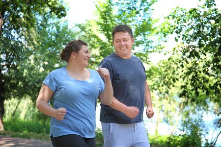 Couple en surpoids qui court dans un parc verdoyant