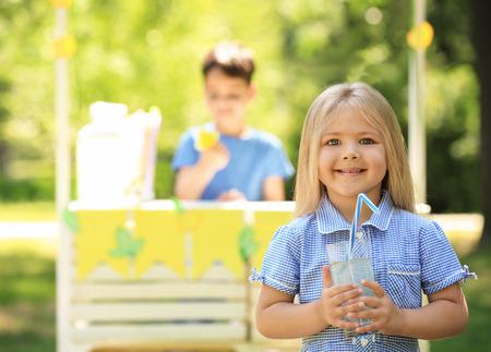 Adorable niña sosteniendo un vaso de limonada en el parque Foto de archivo