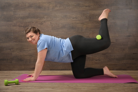 Overweight young woman training against wooden wall