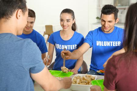 Teen volunteers serving food for homeless people indoors Banque d'images - 110927783