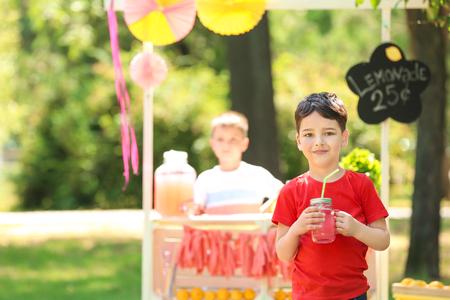 Adorable little boy with jar of homemade lemonade in park