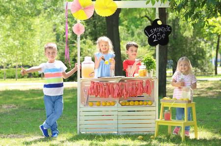Gelukkige kinderen maken limonade op stand in park