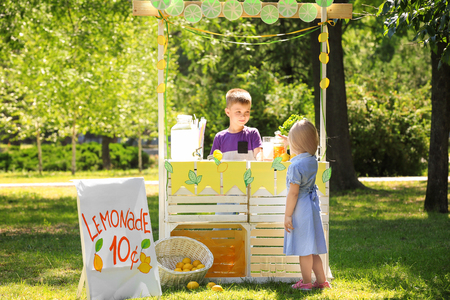 Cute little girl buying homemade lemonade in park