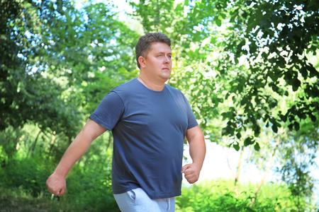 Overgewicht man loopt in groen park Stockfoto
