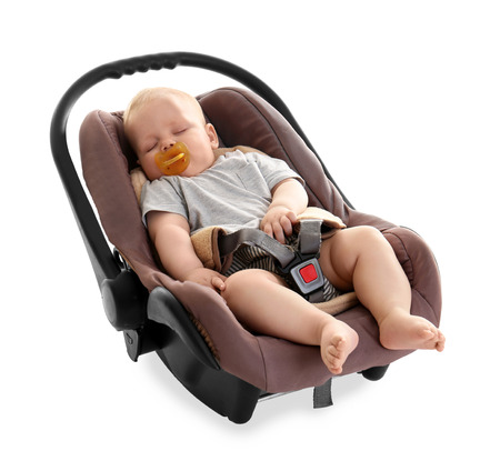 Adorable baby with pacifier sleeping in child safety seat isolated on white Foto de archivo