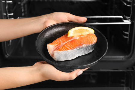 Woman holding salmon steak with lemon in portioned frying pan near oven Imagens