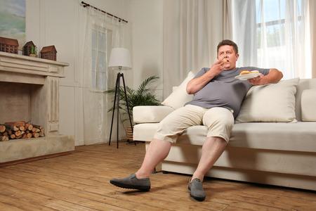 Hombre joven con sobrepeso comiendo dulces en el sofá en casa