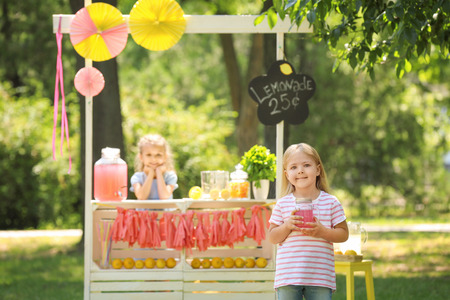 Adorable little girl with jar near lemonade stand in park Stockfoto