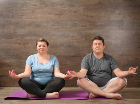 Overweight couple training together against wooden wall