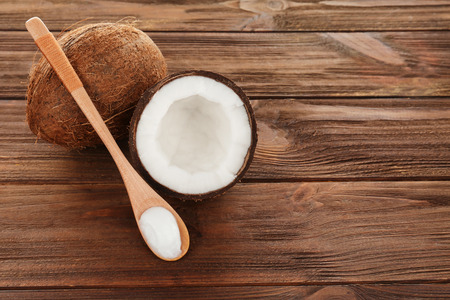 Spoon with coconut oil on wooden background
