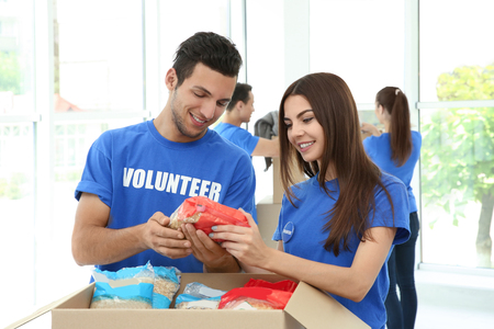 Team of teen volunteers collecting food donations in cardboard box indoors Stockfoto