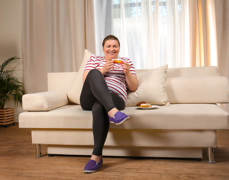 Overweight young woman eating sweets on sofa at home Banco de Imagens