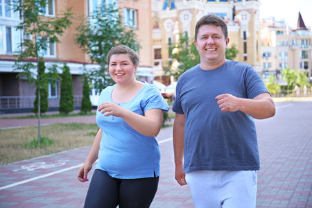Overweight couple running, outdoors Banco de Imagens