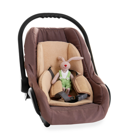 Cute toy in child safety seat isolated on white