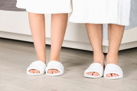 Couple in bathing slippers at home