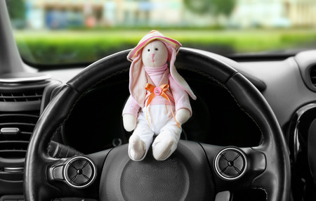 Adorable toy on steering wheel. Travelling with little child concept