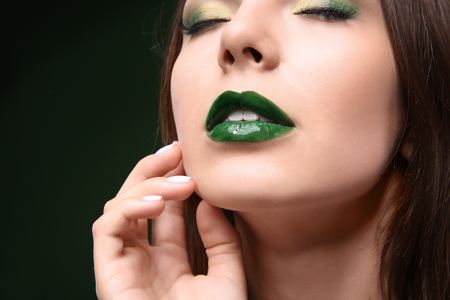 Young beautiful woman with fancy green makeup on dark background
