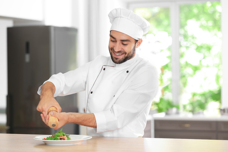 Young male chef adding spices to salad in kitchen