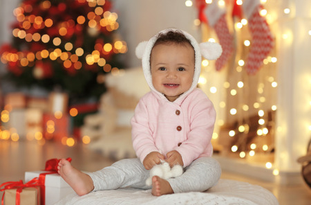 Cute little baby with toy sitting on floor in decorated for Christmas room