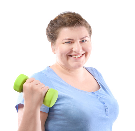 Overweight young woman with dumbbell on white background