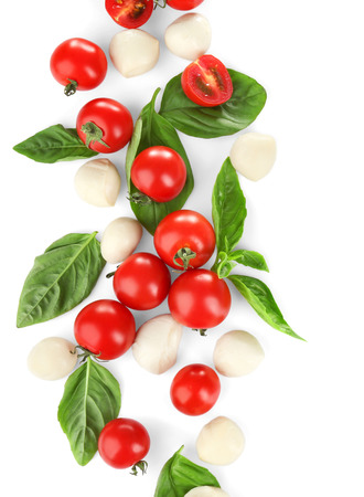 Mozzarella cheese balls, cherry tomatoes and green fresh organic basil isolated on white