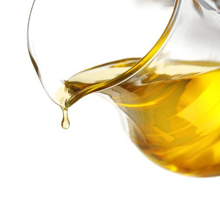 Wylewanie oleju do gotowania ze szklanego dzbanka, na białym tle Zdjęcie Seryjne