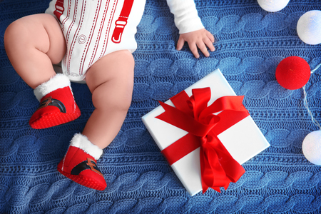 Cute little baby with gift box and garland on knitted fabric 免版税图像 - 110898879