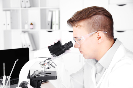 Young male researcher carrying out scientific research in lab Фото со стока