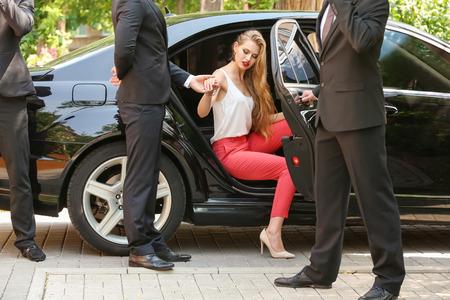 Garde du corps aidant une jeune femme d'affaires à sortir de la voiture Banque d'images