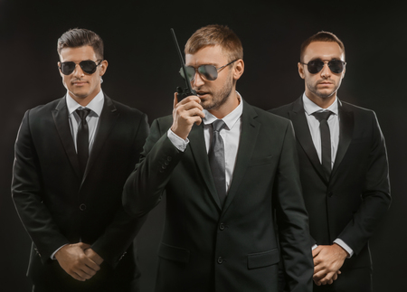 Handsome bodyguards on dark background Standard-Bild