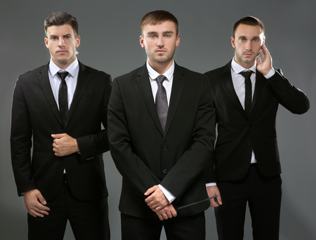 Handsome bodyguards on grey background Standard-Bild