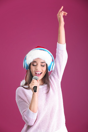 Beautiful young woman in Santa hat singing Christmas songs on color background 免版税图像