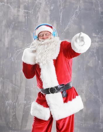 Santa Claus listening to music on grunge background Stock Photo