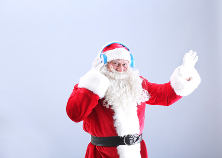 Santa Claus listening to music on color background Stock Photo